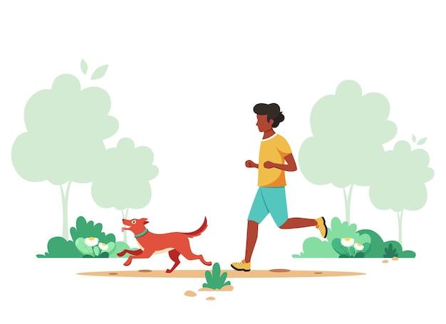春の公園で犬とジョギングしている黒人男性。健康的なライフスタイル、スポーツ、アウトドアアクティビティ