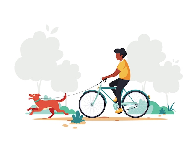 Black man riding bike with dog in the park.