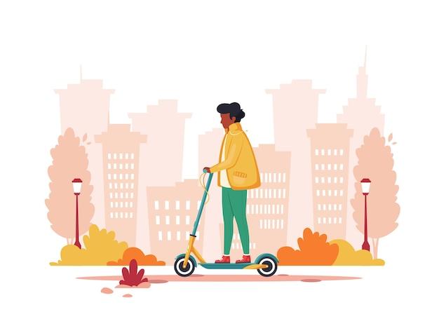 秋に電動キックスクーターに乗る黒人男性。エコ輸送のコンセプト。