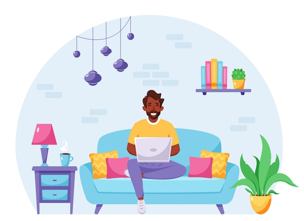 Black man sitting on a sofa and working on laptop freelancer home office