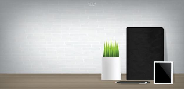 Черный блокнот и пустая фоторамка с декоративным растением в винтажной комнате