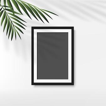 白い背景の上のヤシの葉と黒のフォトフレーム。ベクター