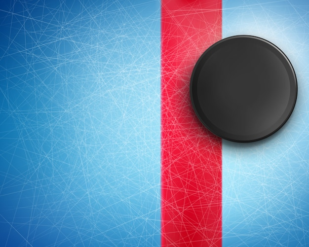 Black rubber puck on the blue ice