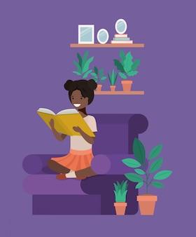 Black student girl sitting reading book in livingroom