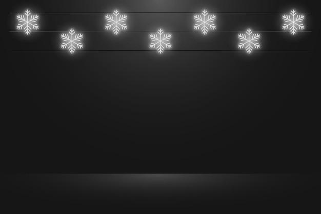 クリスマスと新年のプレゼンテーションのための輝くネオンの雪片をぶら下げて黒いスタジオの背景