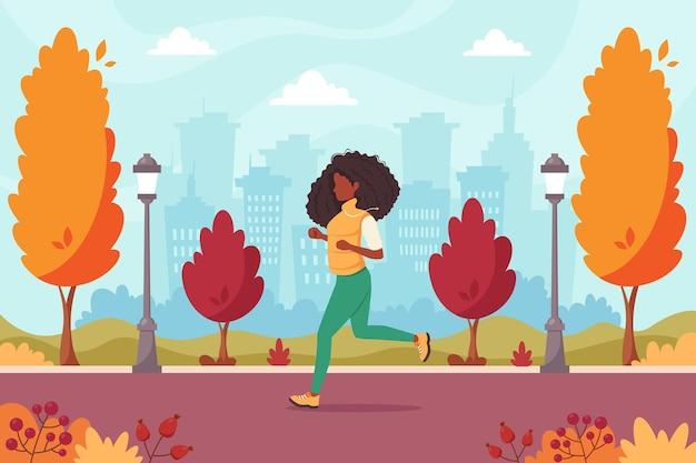 秋の公園でジョギングしている黒人女性健康的なライフスタイル