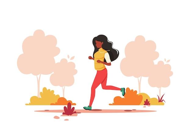 가을 공원에서 조깅하는 흑인 여성. 건강한 라이프 스타일, 스포츠, 야외 활동.
