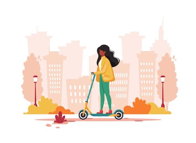 秋に電動キックスクーターに乗る黒人女性。エコ輸送のコンセプト。
