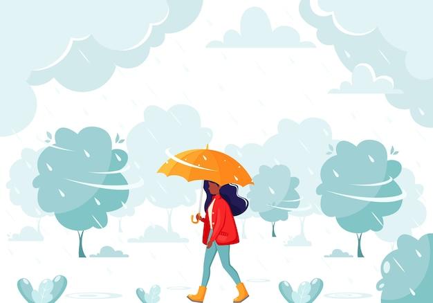 雨の中に傘の下を歩く黒人女性。秋の雨。秋の野外活動。雨の中に傘の下を歩く女性。秋の雨。秋の野外活動。