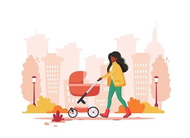 秋に乳母車で歩く黒人女性。アウトドアアクティビティのコンセプト。