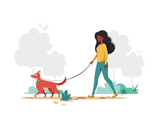 공원에서 강아지와 함께 산책하는 흑인 여성. 야외 활동 개념.