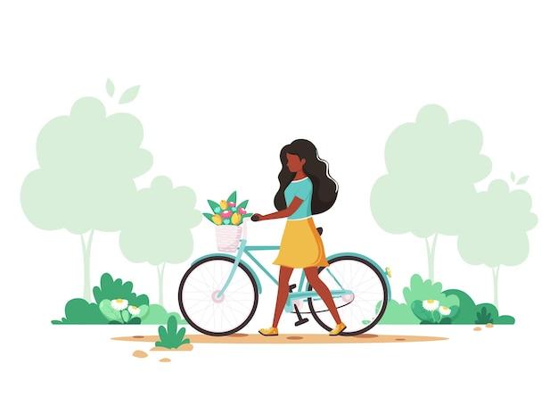 봄의 공원에서 바구니에 꽃과 자전거와 흑인 여성