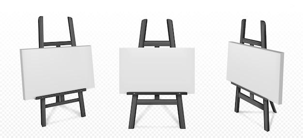 正面と角度のビューで白い帆布と黒い木製イーゼル。絵画用の空白のボード、透明な背景に分離されたアートを描くための三脚と木製スタンドのリアルなモックアップ