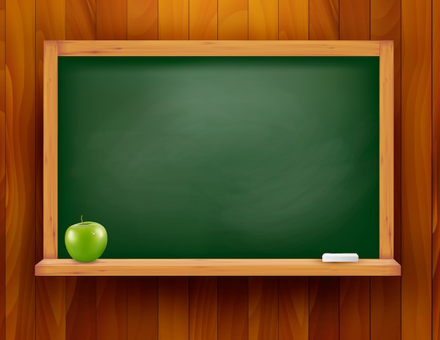 Blackboard with green apple on wooden background.