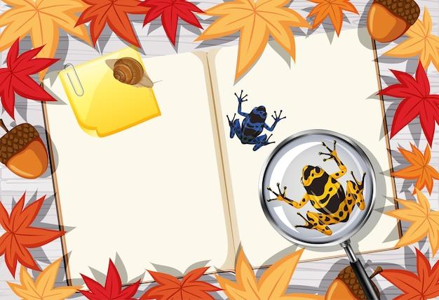 나뭇잎과 개구리 요소와 사무실 작업 테이블 상위 뷰에 빈 책 페이지