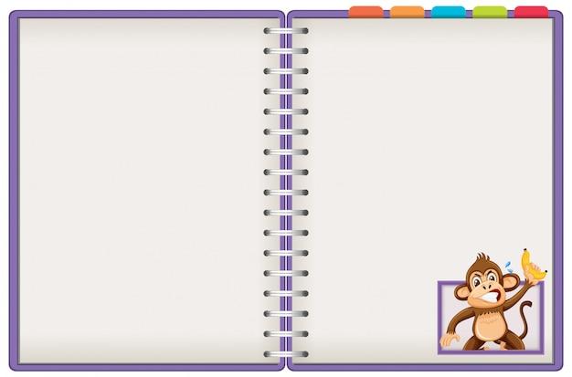 小猿が白い背景で隔離の空白のノートブック