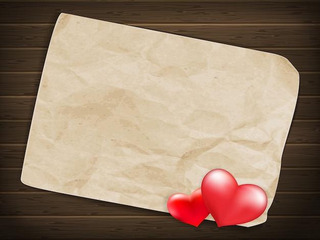 空白の古い一枚の紙と木製の背景上のヴィンテージの手作りのバレンタインデーグッズ心。