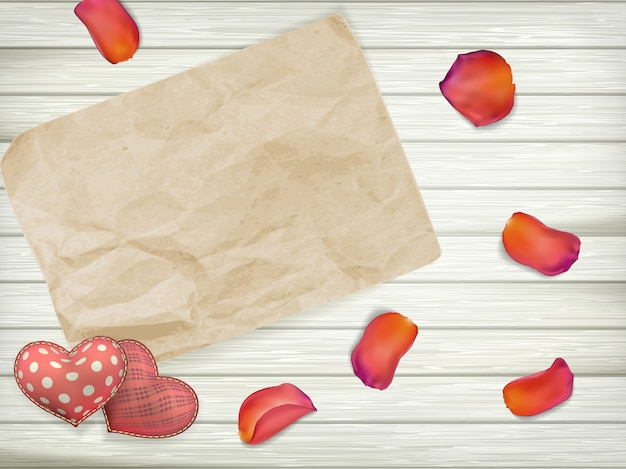 Blank old piece of paper and vintage hand maded valentines day toy hearts over wooden background.