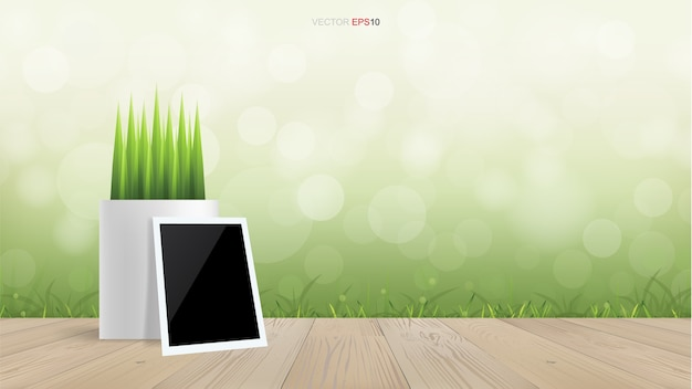 Blank photo frame and flower pot on wooden terrace