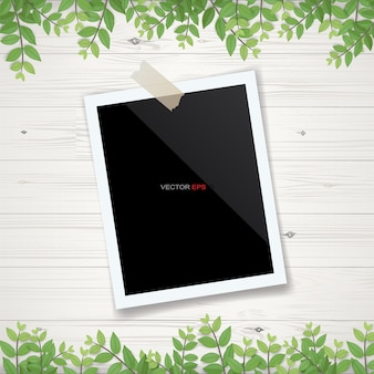 Blank photo frame or picture frame with framing of green leaves and wooden texture background