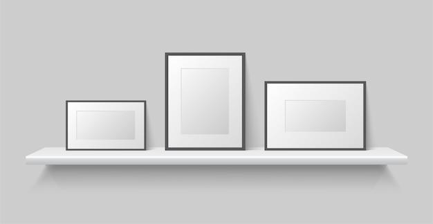 空白のフォトフレームのモックアップは棚に立っています。本棚の黒と白の空のフォトフレームテンプレート。
