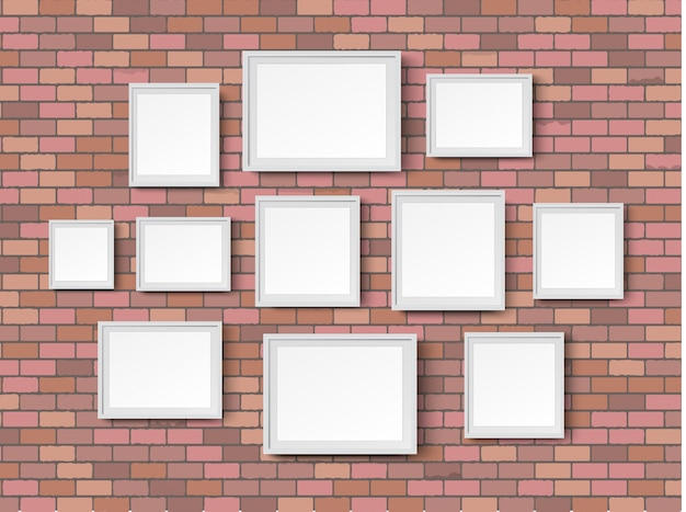 Blank picture frames on red brick wall