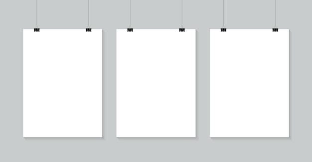 バインダークリップにぶら下がっている空白のポスター。 a4ホワイトペーパーシートは、プロモーションや広告用のクリップバナー付きのロープにぶら下がっています。