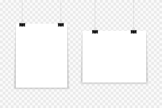 バインダークリップにぶら下がっている空白のポスター。 a4ホワイトペーパーシートがクリップ付きのロープにぶら下がっています。プロモーション用のバナー。