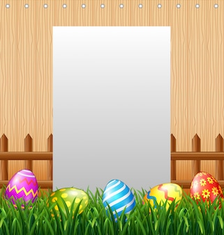 Blank sign in the grass field with decorated easter eggs