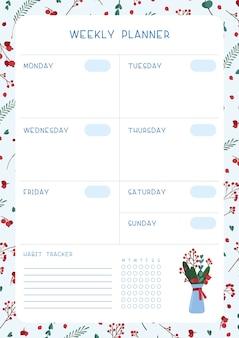 空白のウィークリープランナー。空の冬をテーマにした手帳。クリスマスの象徴的な木の葉、ベリー、花束