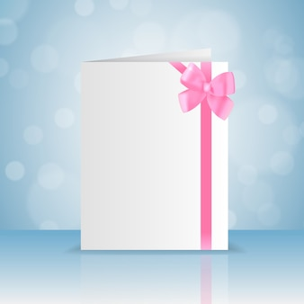 Blank white greeting card with romantic pink bow and ribbon with bokeh flat
