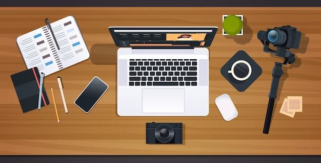 블로거 또는 비디오 편집기 직장 노트북 블로깅 개념 편집을위한 응용 프로그램의 인터페이스가있는 데스크탑 상단 각도보기 수평 기록을위한 전문 디지털 카메라