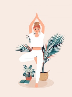 Blond girl who practices yoga in tree pose surrounded by pots of tropical plants