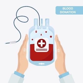 手に赤いドロップが付いた血液バッグ。寄付、輸血の概念。