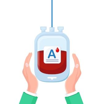 흰색 배경에 고립 손에 빨간 드롭 혈액 가방.