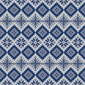 Синий и белый вязаный фон со снежинками и традиционным скандинавским орнаментом.