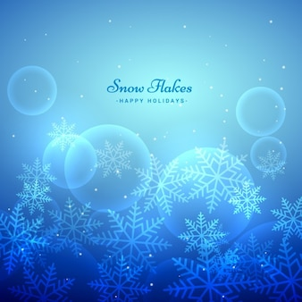 Blue and bokeh background with snow flakes