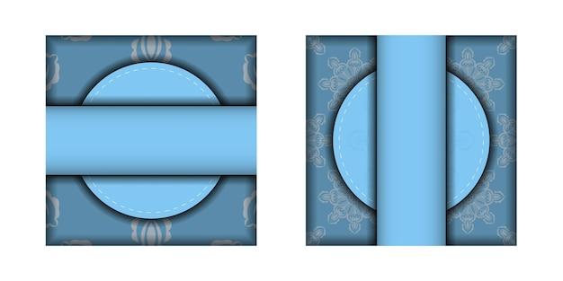 あなたのブランドのための曼荼羅の白い飾りが付いている青い色のチラシ。