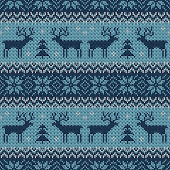 Blue knitted seamless pattern with deers and traditional scandinavian ornament.