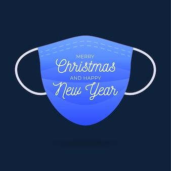 メリークリスマスのテキストが付いた青い医療用フェイスマスク。クリスマスの挨拶の傾向。コロナウイルスの発生。ヘルスケアの概念。