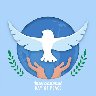 Blue paper cut circle shape earth globe background with hands releasing dove and green olive leaf branches for international day of peace.