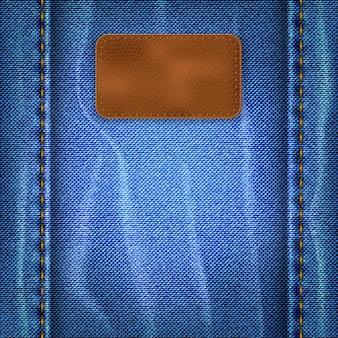 Синий потертый джинсовый фон с кожаной этикеткой
