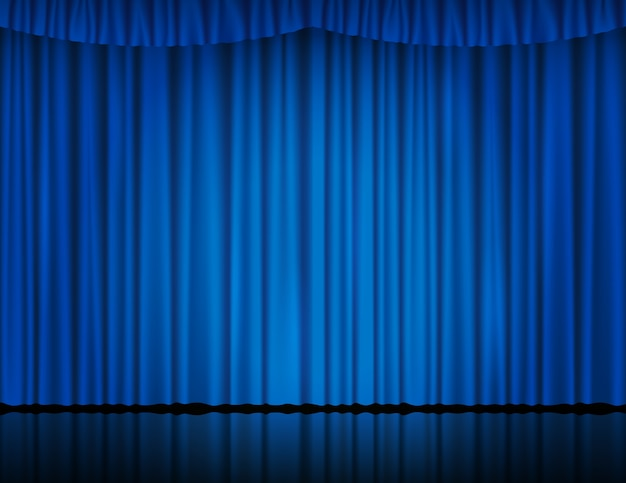 Blue velvet curtain in theater or cinema lit by searchlight