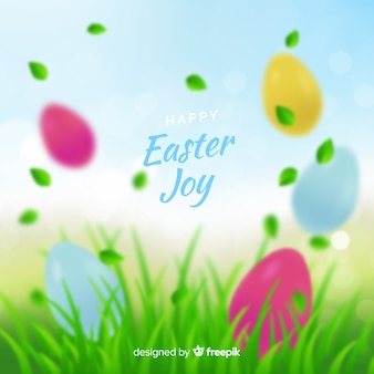 Blurred eggs on grass easter day background