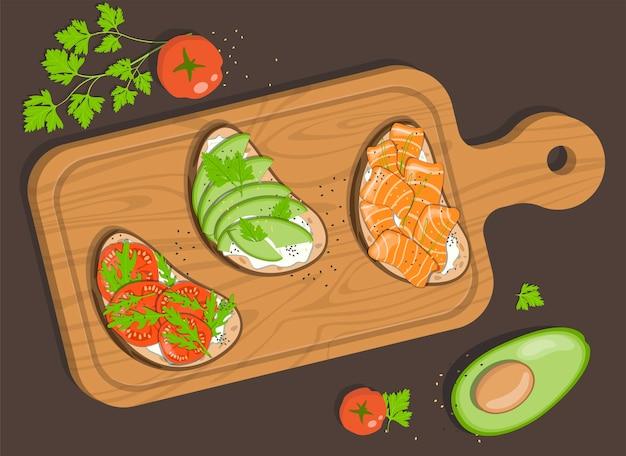 Доска с тремя брускеттами с творогом, красной соленой рыбой, авокадо, помидорами и зеленью.