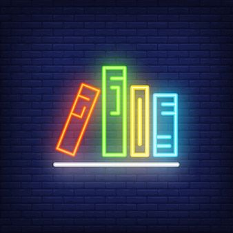 Books on shelf neon sign. Various colorful in row on shelf. Night bright advertisement.