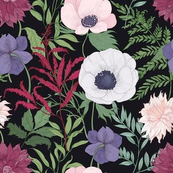 黒の背景に咲く庭の花と植物のシームレスなパターン。