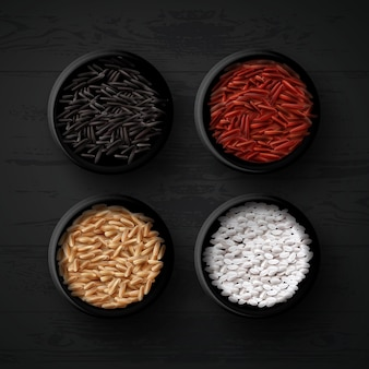 Bowls with different varieties of rice: red, brown, wild and white or for sushi on black wooden background, top view