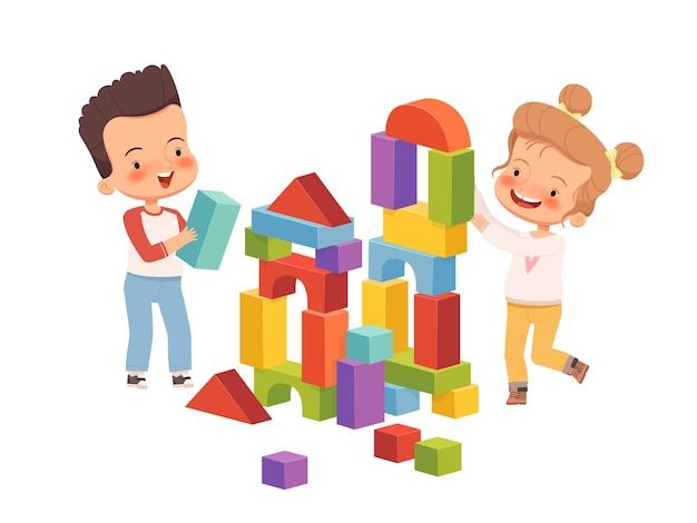 소년과 소녀는 웃고 있으며 어린이 블록의 탑을 짓고 있습니다. 아이들은 함께 친절하고 재미있게 놀습니다. 흰색 배경에 고립.