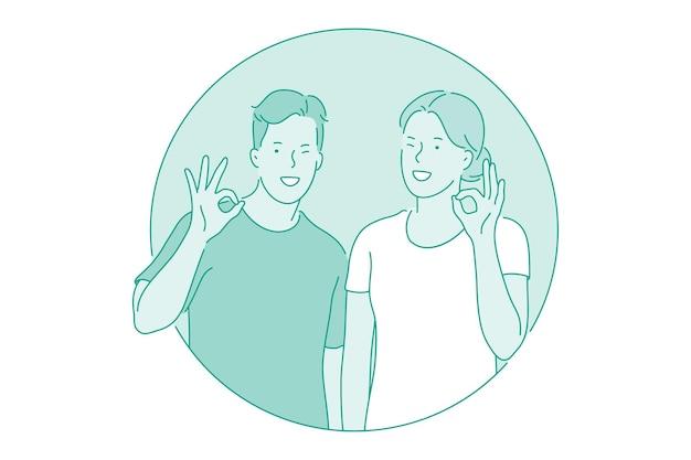 男の子と女の子の漫画のキャラクターが立って、okジェスチャーを示しています